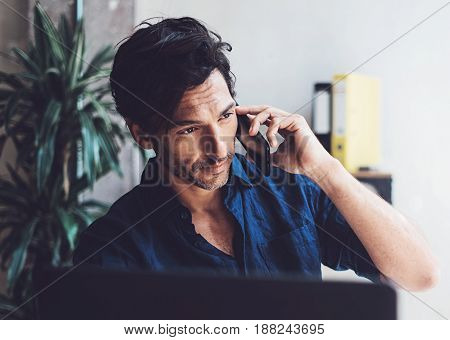 Portrait of Handsome young businessman working at sunny work place on laptop.Smiling Man making mobile phone conversation while sitting at the wooden table.Blurred background.Horizontal