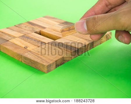 Finger is moving wooden block to fulfil in empty slot