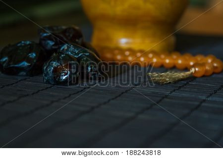 Date fruits or datulas with muslim beads for holy month of ramadan to break fasting from sunrise to sundown.