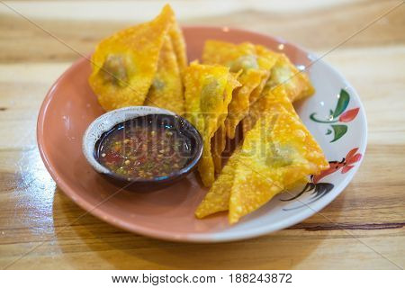 Deep fried crispy dumpling strips with spicy sauce on plate Thai snack food