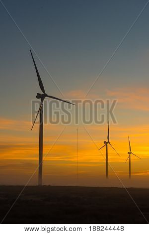 Silhouettes of wind turbines and a communications tower at dawn near Hopefield a town in the Western Cape Province