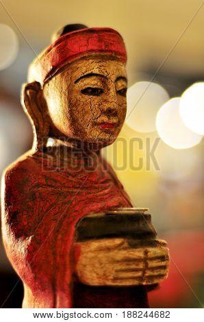 Burmese monk wood carvings on the Bokeh background.