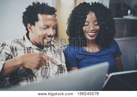 Closeup view of African couple having rest at a home: black girl sitting on sofa, holding touch tablet and laughing, looking through travel photos together with her husband who is sitting close to her