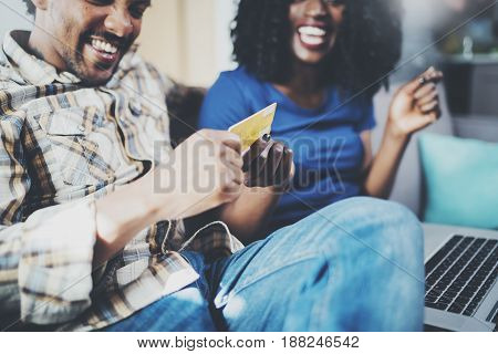 Happy young african american couple sitting on sofa at home and shopping online through mobile computer by credit card. Horizontal, blurred background