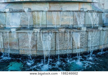 Many streams of water cascade down this fountain.