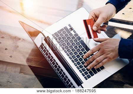 Closeup view of Man holding credit card in hand and typing laptop keyboard while sitting at the wooden table.Reflections on glass surface.Top view.Horizontal.Visual effects