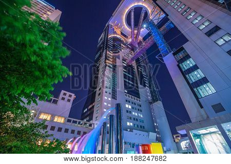 Osaka, Japan - April 28, 2017: prospective view of Umeda Sky Building and fountains in Kita-ku district by night. The Floating Garden Observatory is one of the most popular attractions in Osaka