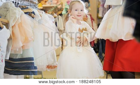 Portrait of a little girl who holds a white ball gown in the children's clothing store.