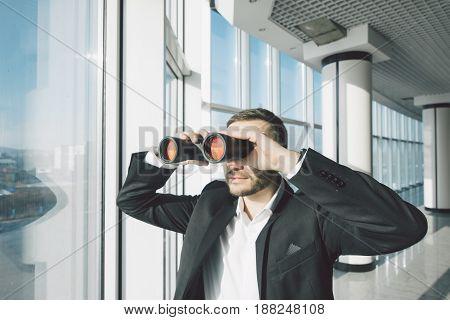 Business Man Looking With Binoculars Over Panoramic Windows