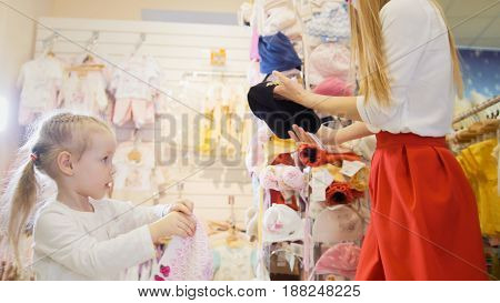 A young mother shows her little black hat in the children's clothing store