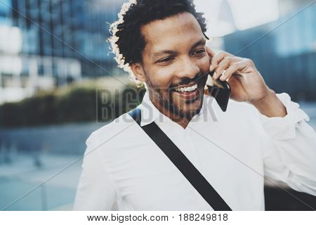 Closeup portrait of smiling American African man using smartphone to call friends at sunny street.Concept of happy young handsome people enjoying gadgets outdoors.Blurred background