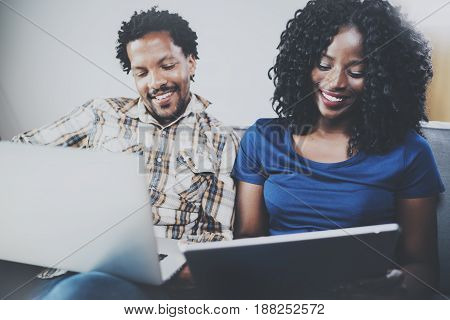 Front view of Happy african american couple relaxing together on the sofa.Young black man and his girlfriend using modern notebooks at home in the living room. Horizontal, blurred background