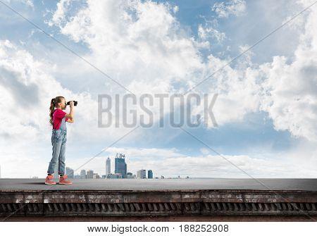 Cute girl of school age on building roof looking in binoculars