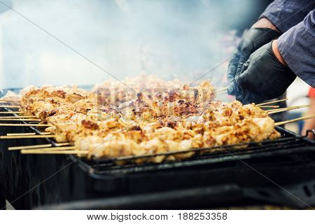 cooking chicken meat on grill in backyard