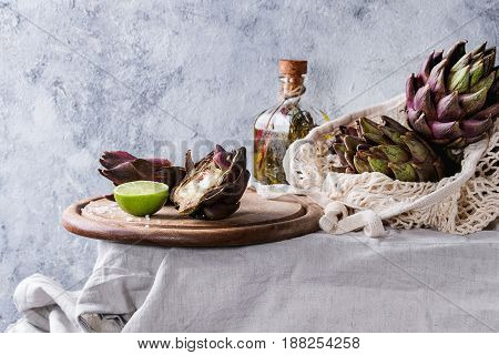 Uncooked whole and sliced organic wet purple artichokes with lime and olive oil on chopping board and in knitted bag on white tablecloth over gray texture background.