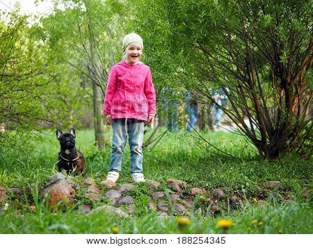 Happy baby laughing. Little girl with dog in Park