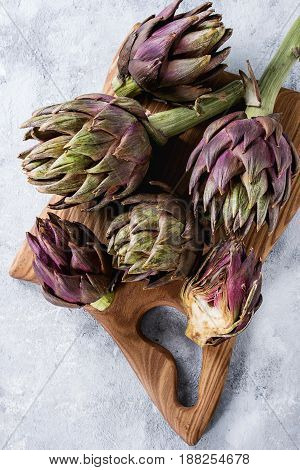 Uncooked whole and sliced organic wet purple artichokes on wooden chopping board over gray texture background. Top view with space