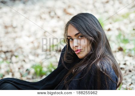 woman with cute smile on young face no makeup long brunette hair in black coat sitting on ground on sunny day outdoors on natural background. Leisure or vacation