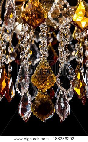 Classic Chandelier for interior decoration of the living room. Large chandelier close-up details decorated with crystals and amber isolated on black background. Gold modern a piece of interior for designers.