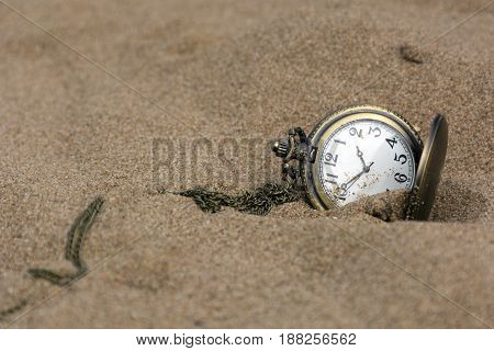 round pocket watch on a chain in the sand time dial