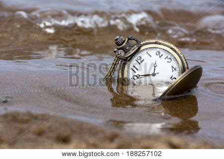 round mechanical pocket watch in the sand under water wave