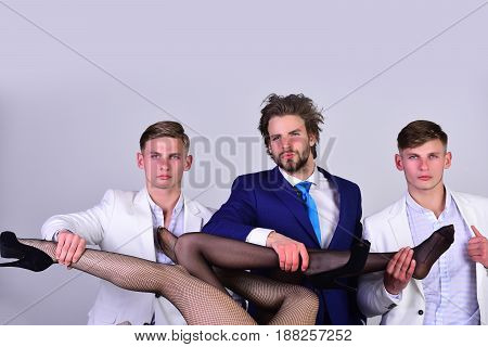 love and relations. group of people men or businessmen in jacket and female sexy legs in fashionable shoes and tights on grey background love and relations power boss office romance sexual services copy space