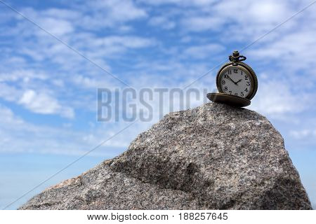 round pocket watch on a stone against the sky with clouds dial hands