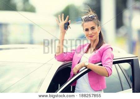 Attractive woman hand out window car holding car key.