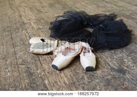 Ballet shoes and black tutu on a old wooden background. Top view photo. Horizontal.