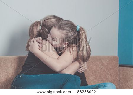 Daughter hugging his mother at home. Concept of couple family is in sorrow.