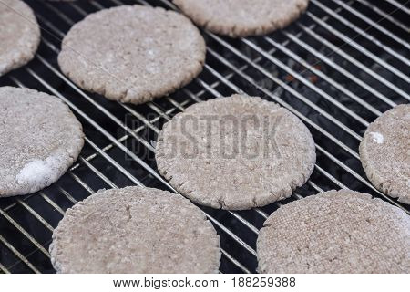 Frozen Hamburger Patties on a Barbecue close up.