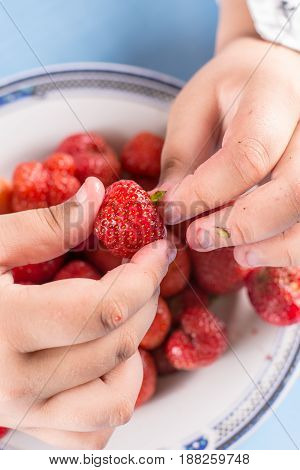 Kid cleaning strawberries with hands above plate with strawberries.