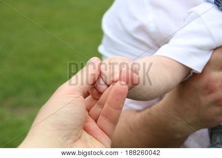 Newborn baby boy holds his fathers hand offering him love and security