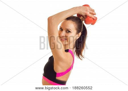 Portrait of beautiful sportswomen that looks into the camera keeps the dumbbells above head and smiling close-up isolated on white s