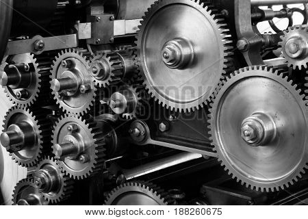 Gray scale photo of gears in a huge mechanism