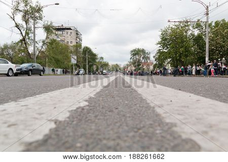 City road dividing strip. People are standing on the side of the road