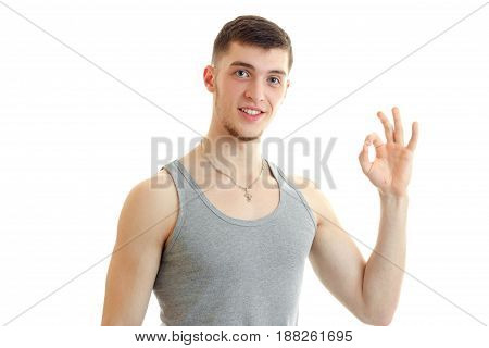 young sports handsome guy smiles and hand dest Okey isolated on white background