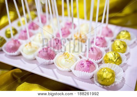 Different colourful candies on a stick. Bonbons wrapped in golden foil. Yellow pink white. Extremely tasty and delicious desserts. Sweets full with sugar. Unhealthy food diet.