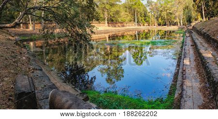 Small artificial lake near Baphuon Temple in Angkor Complex, Siem Reap, Cambodia. Pile of stones on road to pond in foreground. Ancient Khmer architecture and famous Cambodian landmark, World Heritage