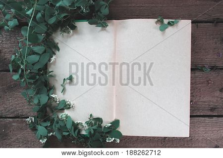 Open book with branches and flowers background