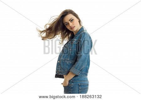 charming young girl in jeans jacket looks straight and her hair fly through the air isolated on white background