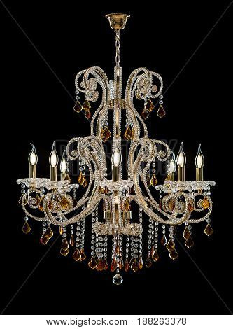 Classic Chandelier for interior decoration of the living room. Large chandelier decorated with crystals and amber isolated on black background. Gold modern a piece of interior for designers.