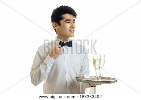 charming young waiter smiles corrects hand bow tie and holds a tray with glasses of wine isolated on white background