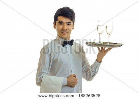 attractive young waiter raised his hand tray with two glasses and smiling isolated on white background