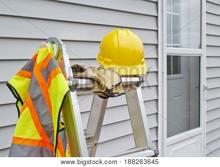 Work gear on step ladder with house siding background