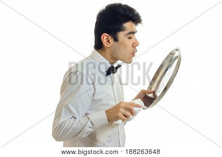 the young waiter stands sideways and blowing on a tray in the hands of a close-up is isolated on a white background
