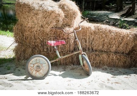 Children's bicycles against the background of a haystack .