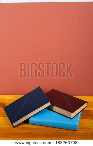 Multi-colored books on a wooden table and red background. Back to School.