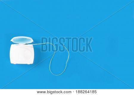 Dental floss in container on blue background.