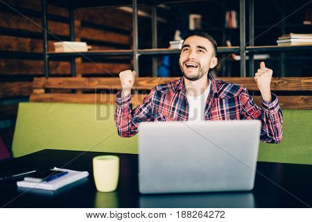 Man In Red Shirt Sitting By The Table With Laptop With Victory Emotions In Office. Coworking
